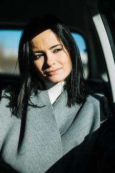 Moderne geschäftsfrau, die im auto sitzt