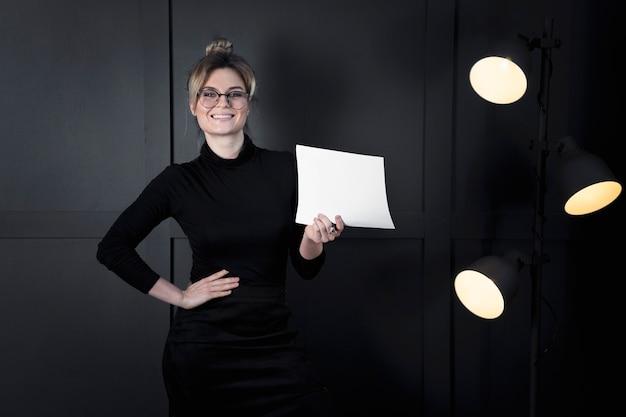 Moderne geschäftsfrau, die papiere im büro hält