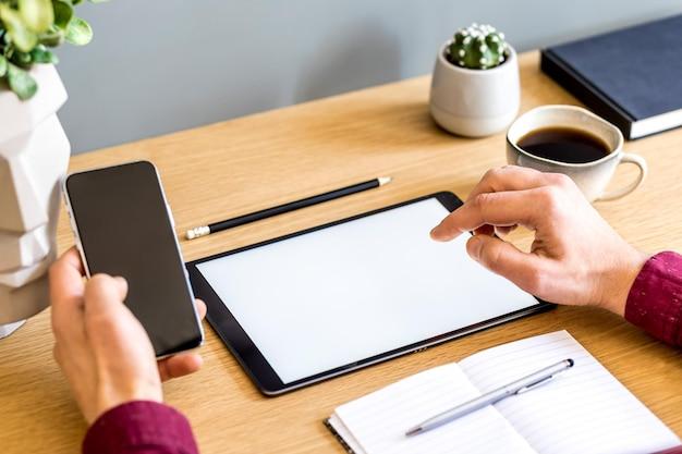 Moderne geschäftskomposition im heimbüro mit freiberufler, tablet-bildschirm, pflanzen, notizen, handy und bürobedarf im stilvollen konzept der wohnkultur.