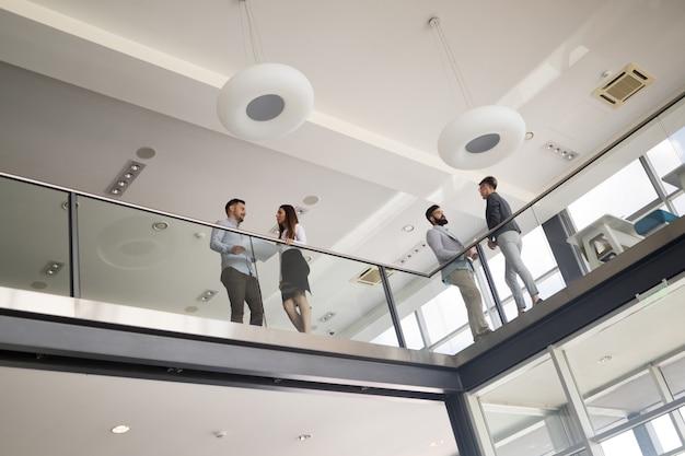 Moderne geschäftsleute, die auf treppen in der glashalle im bürogebäude gehen