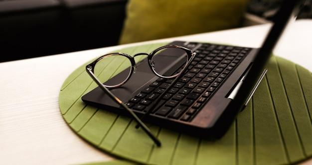 Moderne gläser der geschäftsfrau, die auf notizbuch auf tisch im café liegt. freiberufliche arbeit im restaurant.