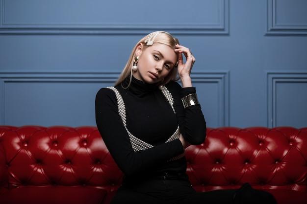 Moderne glamouröse junge frau, die in einem schwarzen hemd in einem modischen weißen perlenoberteil mit eleganten perlenhaarspangen drinnen nahe einer blauen wand aufwirft