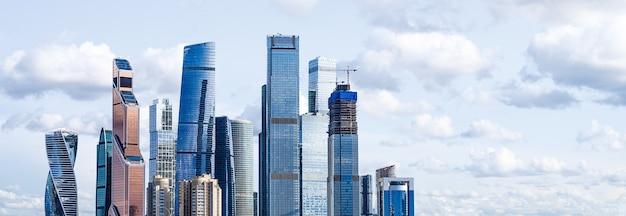 Moderne glasgebäude wolkenkratzer im finanzviertel der stadt über blauem himmel mit wolkenhintergrund