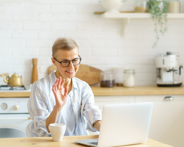 Moderne, glückliche ältere frau mit brille, die beim online-studium mit der webcam auf dem laptop winkt