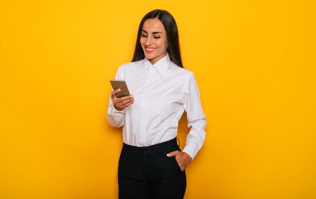 Moderne glückliche erfolgreiche selbstbewusste geschäftsfrau in einem weißen hemd mit smartphone posiert auf gelbem hintergrund yellow