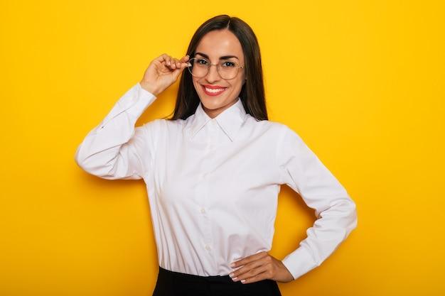 Moderne glückliche erfolgreiche selbstbewusste geschäftsfrau in einer weißen hemdbrille posiert auf gelbem hintergrund yellow