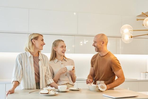 Moderne glückliche familie, die das frühstück zusammen genießt, während sie im kücheninnenraum am tisch steht