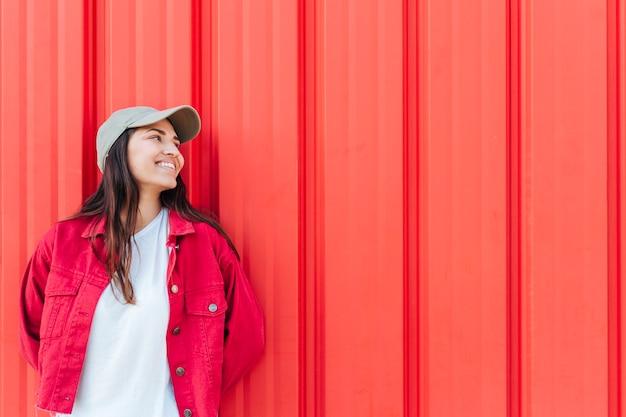 Moderne glückliche frau, die weg gegen roten hintergrund schaut