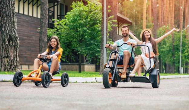 Moderne glückliche junge touristenfamilie im urlaub, die auf fahrrädern reitet und spaß zusammen hat