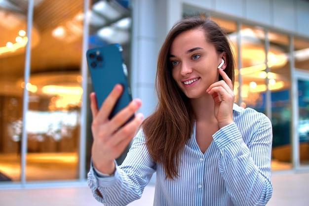 Moderne glückliche lässige intelligente tausendjährige frau, die drahtlose kopfhörer mit smartphone für videoanruf und fern-online-chat trägt