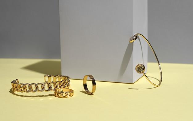 Moderne goldene armbänder und ring auf gelb