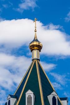 Moderne goldene kuppel mit einem kreuz auf dem grünen dach der orthodoxen christlichen kirche