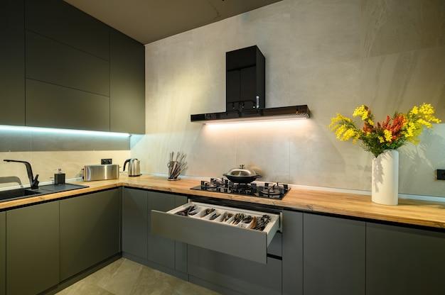 Moderne große luxuriöse dunkelgraue küche mit herausgezogener schublade