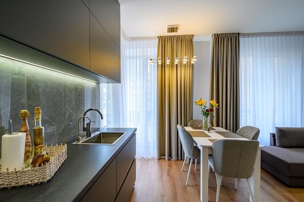 Moderne große luxuriöse dunkelgraue stidio-küche mit esszimmer