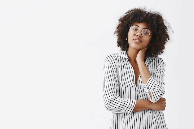Moderne, gut aussehende und stilvolle managerin in gestreifter bluse, die den hals berührt und den kopf neigt, wodurch die massage den ganzen tag über müde vom sitzen und arbeiten ist