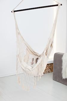Moderne hängematte im wohnzimmerinnenraum. eine gemütliche hängematte in einem stilvollen aufenthaltsraum. stilvolles schlafzimmer mit natürlicher schnurhängematte. wohnung design im loft und rustikalen stil. gemütliches wohnen. ort zum entspannen
