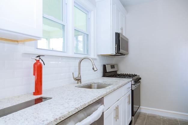 Moderne haushaltsschränke mit neuen geräten und waschbecken in der küche
