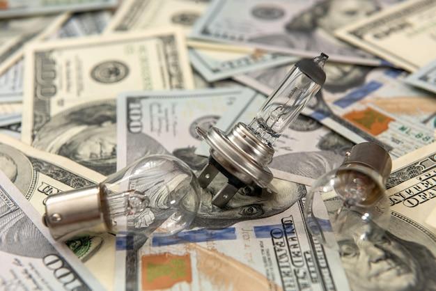 Moderne helle lampenautobirne auf dollarhintergrund, verkaufskonzept