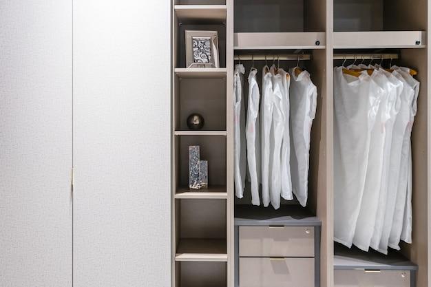 Moderne hölzerne garderobe mit der frauenkleidung, die an der schiene im weg im wandschrank, skandinavische art hängt