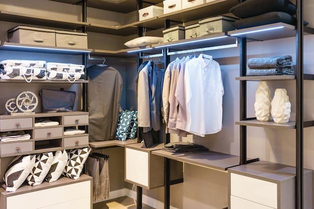 Moderne hölzerne garderobe mit der kleidung, die an der schiene im schrankinnenraum des weges im schrank hängt