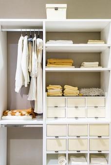 Moderne hölzerne garderobe mit der kleidung, die an der schiene im weg hängt