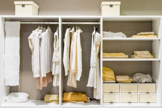 Moderne hölzerne garderobe mit der kleidung, die an der schiene im weg im wandschrankdesigninnenraum hängt