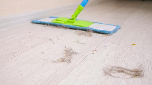 Moderne holzböden von haarfetzen, staub und schmutz mit weichem mopp im raum während des aufräumens reinigen