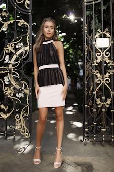Moderne hübsche frau im schwarzweiss-kleid, in der nähe der tore stehend, haare wehend, fröhlich, mode, stil, modell, ereignis, party, rücken, weiße schuhe, absätze, spaß haben, make-up