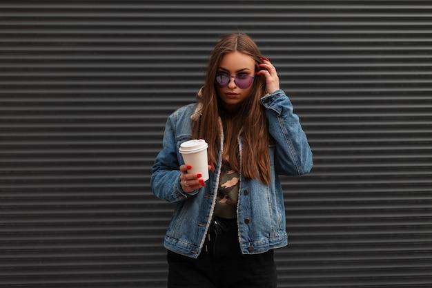Moderne hübsche junge hipster-frau in modischer jeansblaujacke in trendigen lila gläsern mit tasse heißem kaffee steht in der nähe einer grauen wand auf der straße. modisches schönes mädchen, das in der stadt aufwirft.