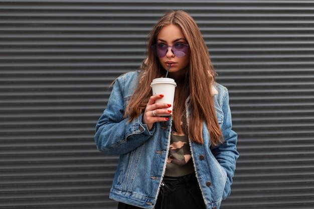 Moderne hübsche modische junge hipster-frau in stilvollen violetten gläsern mit trendiger jeansjacke trinkt süßes leckeres getränk in der nähe der metallgrauen wand in der stadt. schönes mädchenmodell draußen.