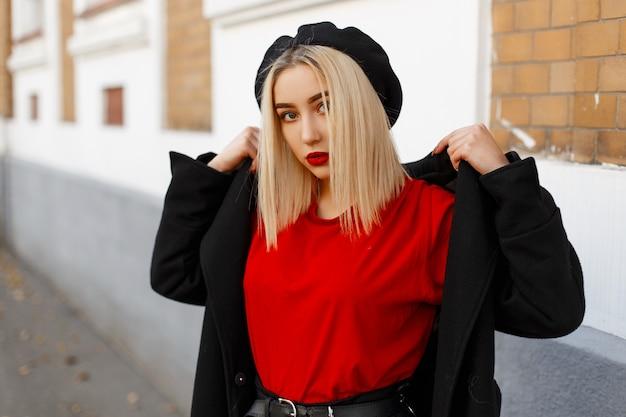 Moderne junge blondine mit einer frisur mit roten sexy lippen in einer eleganten schwarzen baskenmütze in einem langen modischen mantel in einem roten t-shirt, das nahe einem alten gebäude aufwirft