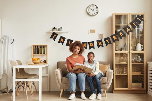 Moderne junge erwachsene frau, die zeit mit ihrem sohn verbringt, der zusammen auf sofa im wohnzimmer sitzt, verziert für halloween und lesebuch, kopienraum