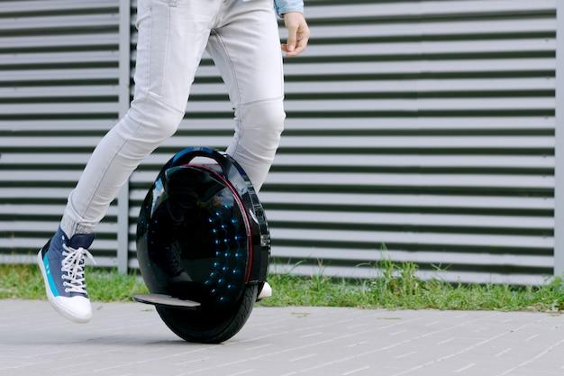 Moderne junge erwachsene männliche geschäftsmann student freiberufler fahren fahren auf ökologischen elektrischen transport futuristischen öko elektrischen einrad roller, balancierende elektrische rad. grüner planet der öko-ökologie.