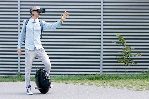 Moderne junge erwachsene männliche geschäftsmann student freiberufler fahren fahren auf ökologischen elektrischen transport futuristischen öko elektrischen einrad roller, elektrische rad mit virtual-reality-brille balancieren