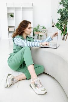 Moderne junge frau, die auf dem boden sitzt und laptop verwendet, um im zimmer mit interieur zu arbeiten