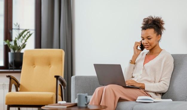 Moderne junge frau, die beim sitzen auf dem sofa arbeitet
