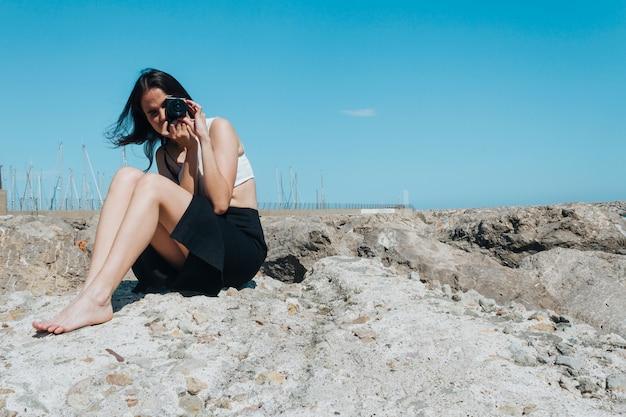Moderne junge frau, die foto mit der kamera sitzt auf felsen an draußen macht