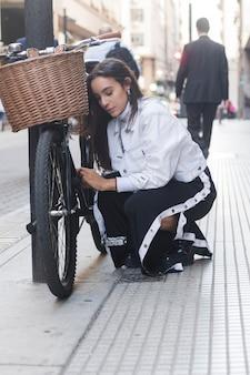 Moderne junge frau, die ihr fahrrad auf straße betrachtet