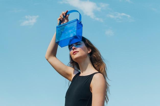 Moderne junge frau, die ihre augen durch blaue plastiktasche gegen himmel abschirmt