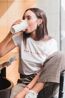 Moderne junge frau, die im café trinkt den kaffee sitzt