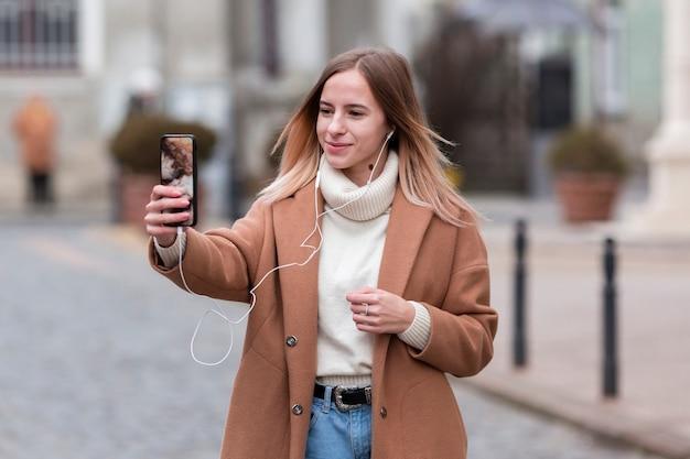 Moderne junge frau, die musik auf kopfhörern beim nehmen eines selfie hört