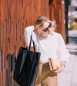 Moderne junge frau, die schwarze handtasche trägt und die bücher weg schauen hält