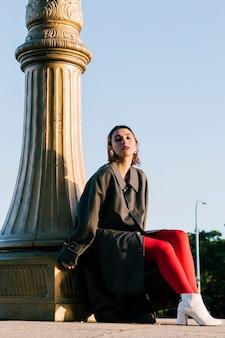 Moderne junge frau, die unter der säule mit rotem strumpf und weißen schuhen sitzt