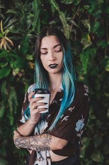 Moderne junge frau mit dem gefärbten haar, das mitnehmerkaffeetasse hält