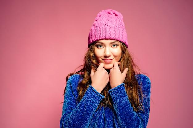 Moderne junge frau, welche die blaue strickjacke und rosa hut aufwirft, lustigen gesichtsausdruck machend trägt.