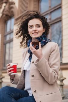 Moderne junge frau, welche die scheibe der wegwerfschale des schokoladenkuchens und -kaffees genießt