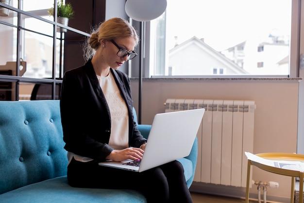 Moderne junge geschäftsfrau, die laptop im büro verwendet