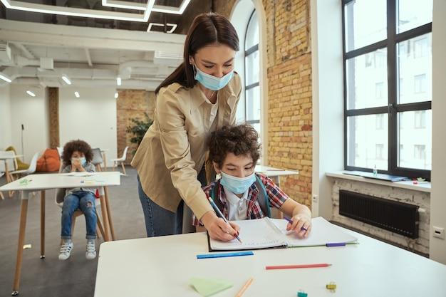 Moderne junge lehrerin, die eine schützende gesichtsmaske trägt, die dem kleinen jungen bei der aufgabe hilft