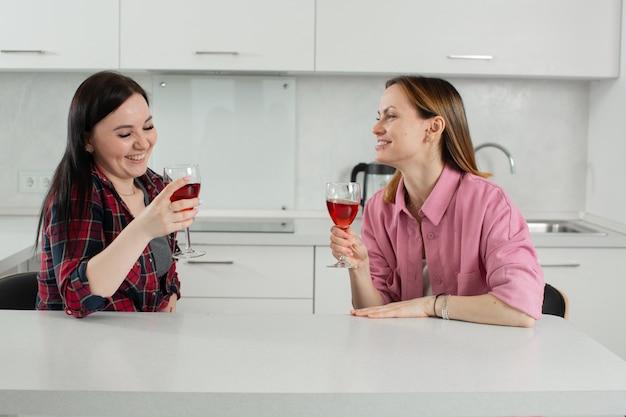 Moderne junge mädchenfreundinnen haben spaß beim trinken von rotwein aus gläsern lachend zu hause in der küche sitzend hochwertiges foto