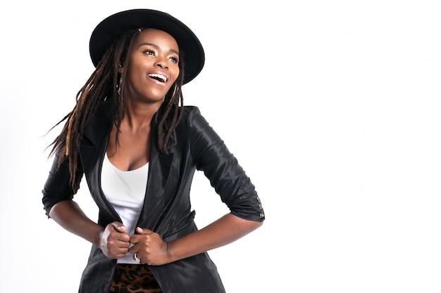 Moderne junge schöne afrikanische frau mit der aufstellung in der schwarzen lederjacke.